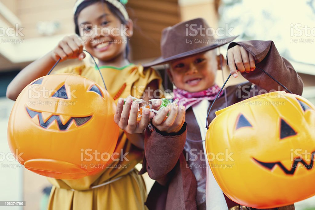 Boy and girl on halloween showing their candy stock photo