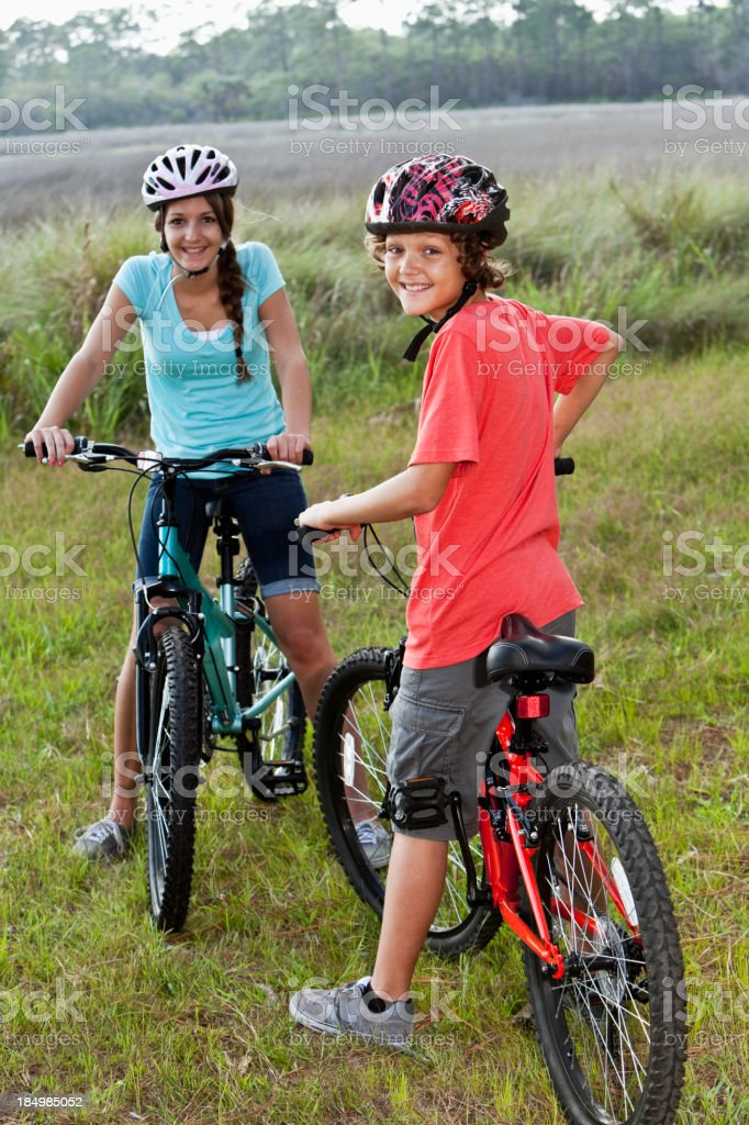 Boy and girl on mountain bikes stock photo