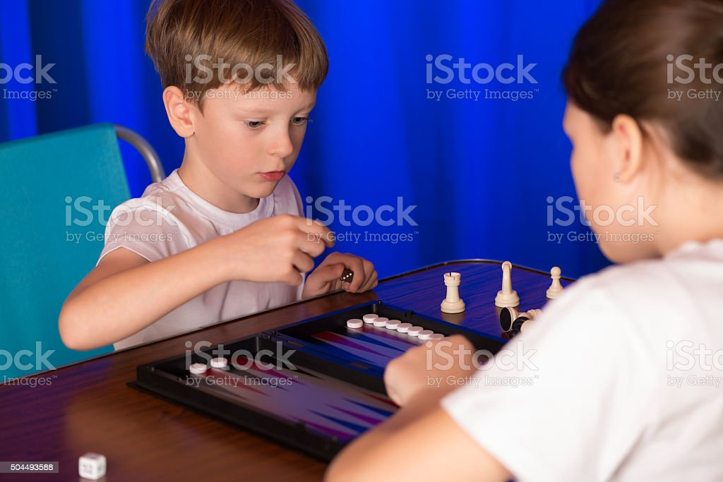 Boy and girl playing a board game called Backgammon stock photo