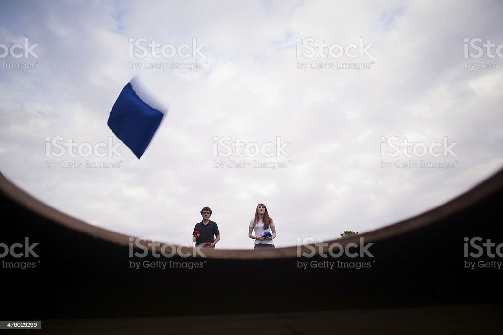 Boy and girl playing beanbag toss at park stock photo