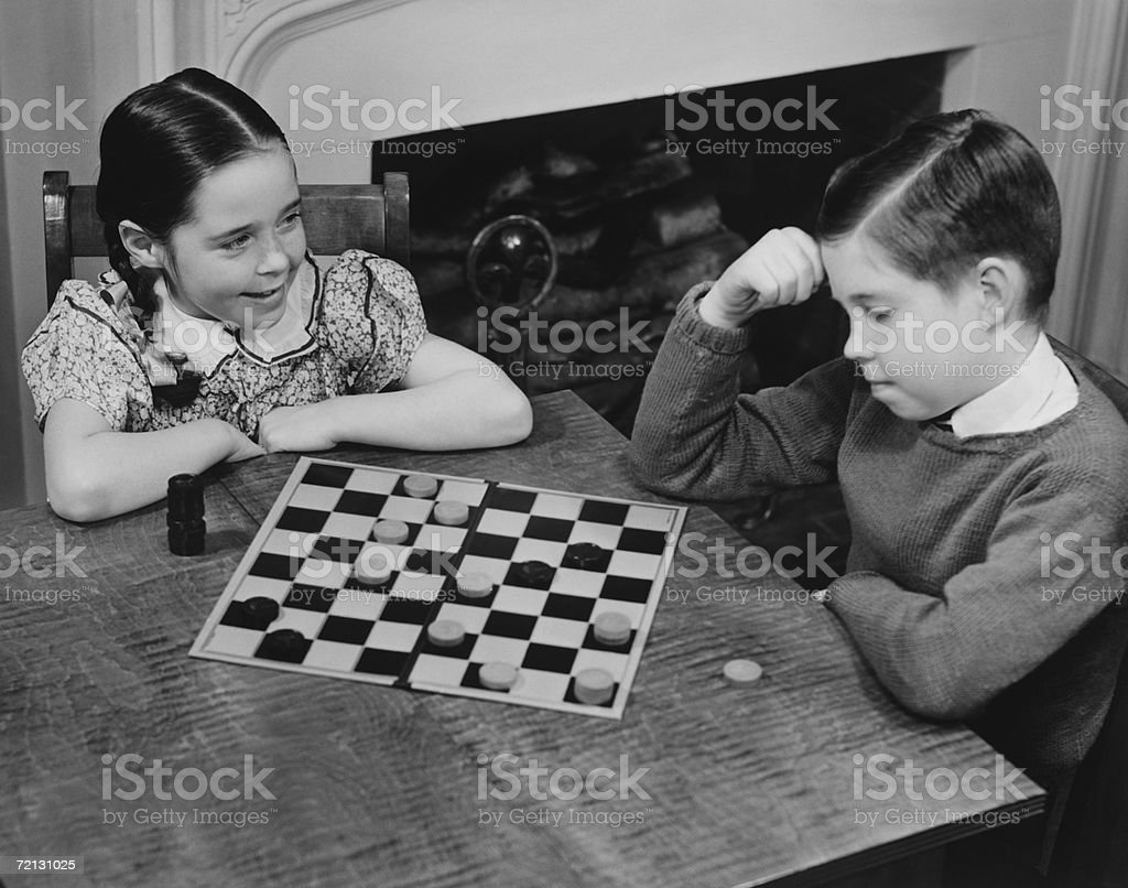 Boy and girl (8-9) playing checkers (B&W), elevated view royalty-free stock photo