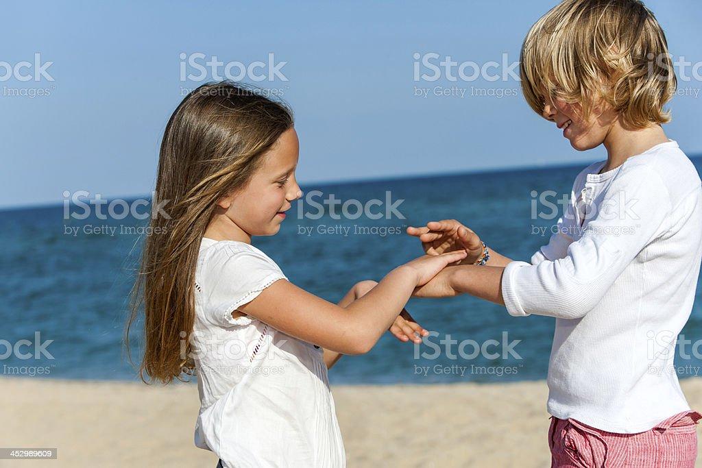 Garçon et fille jouent jeu de main sur la plage. photo libre de droits