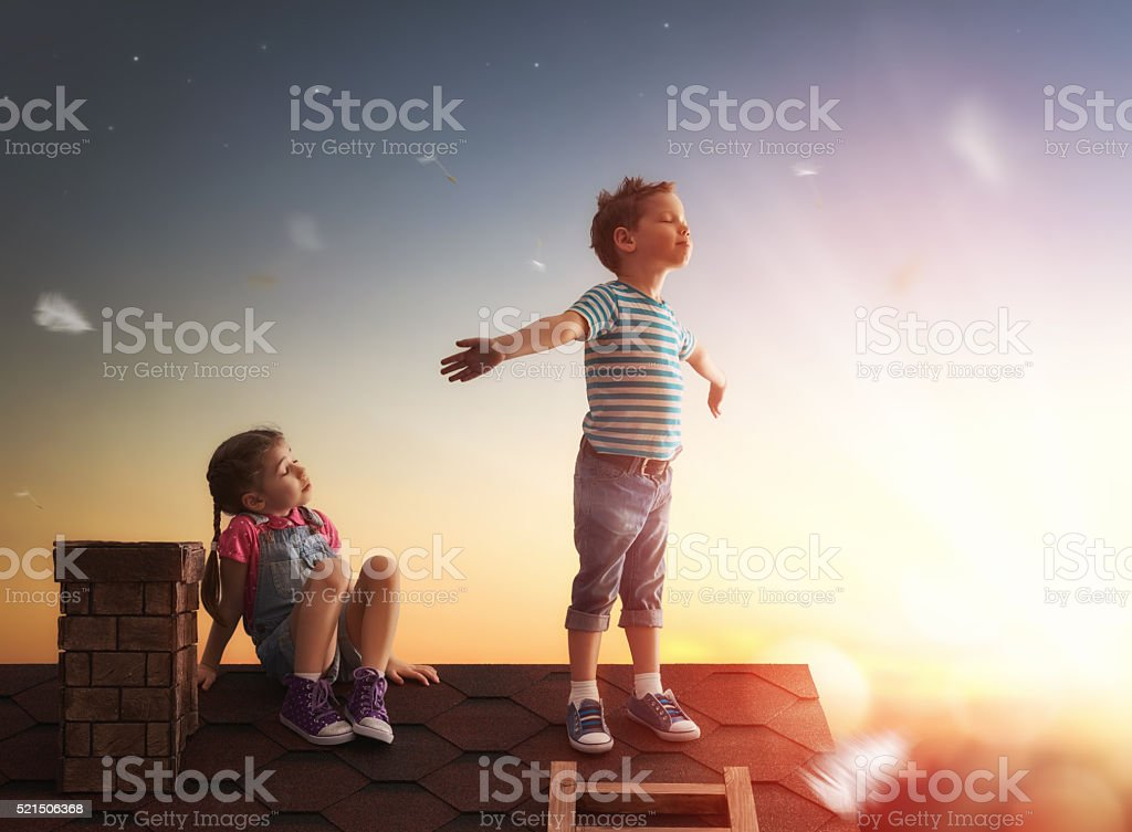 boy and girl playing on the roof stock photo