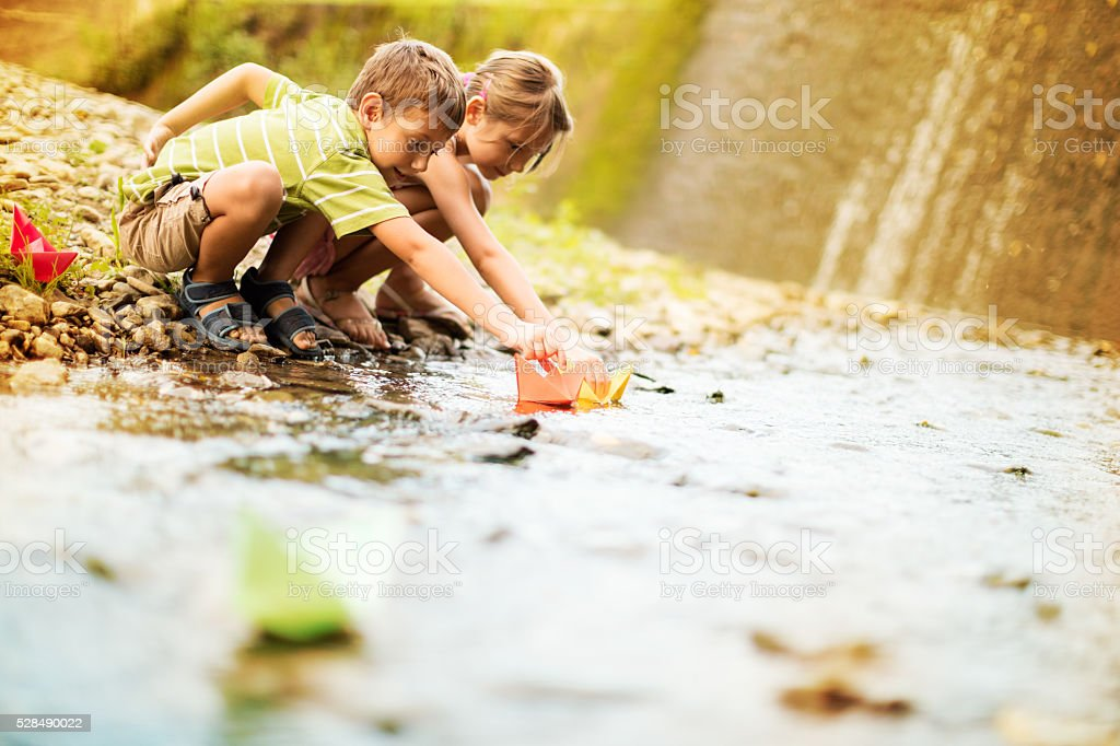 Boy and girl playing paper boats on the river stock photo