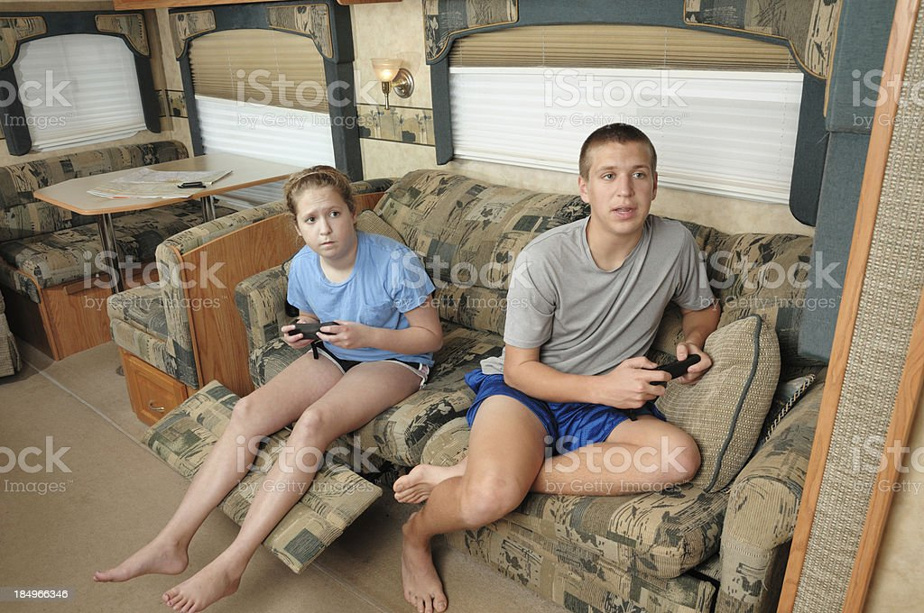 Boy and girl playing video games in rv royalty-free stock photo