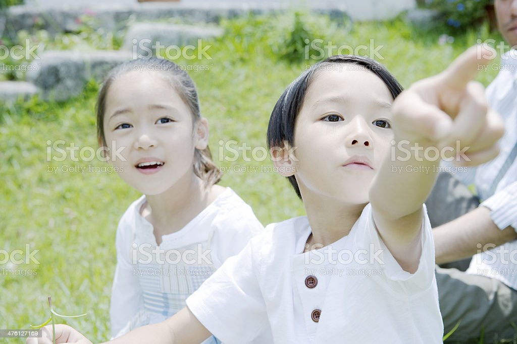 Boy and girl pointing to the distance stock photo