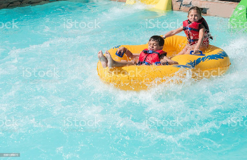 Boy and girl riding in a raft stock photo