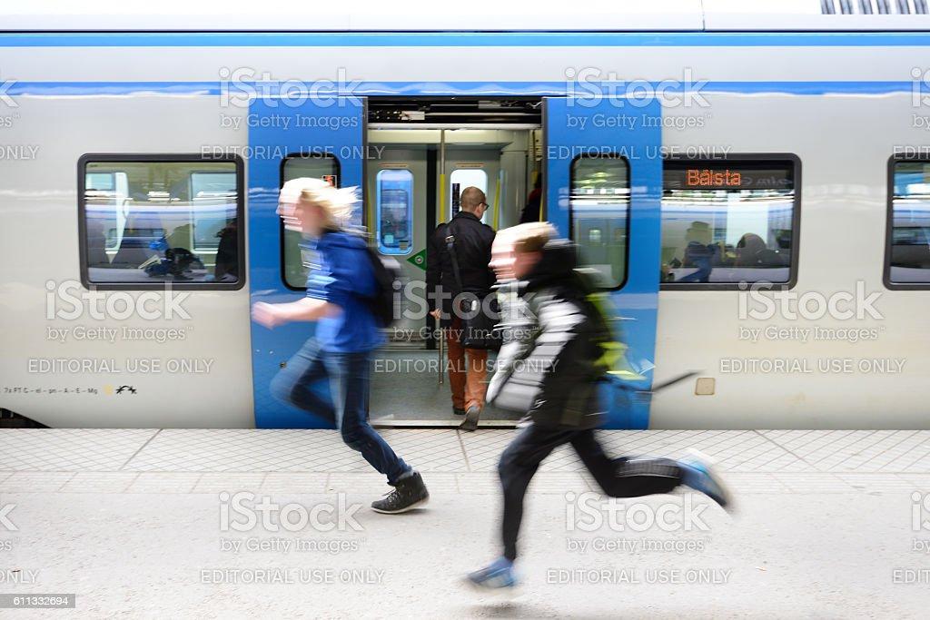 Boy and girl running along commuter train, Centralen stock photo