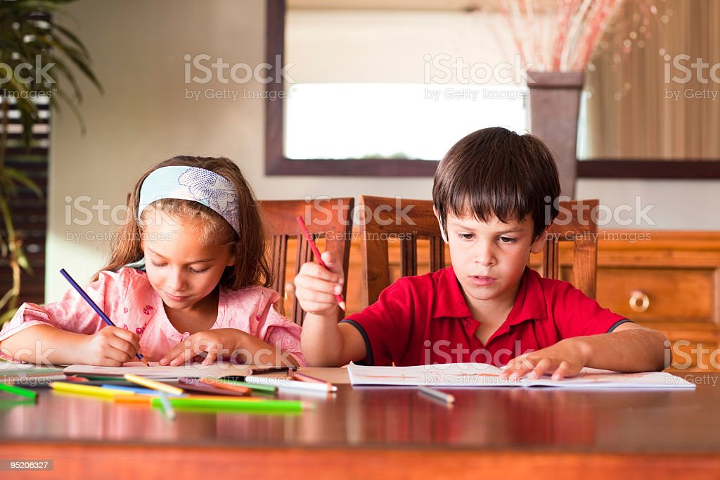 Boy and girl, seated at a table, working on their homework stock photo