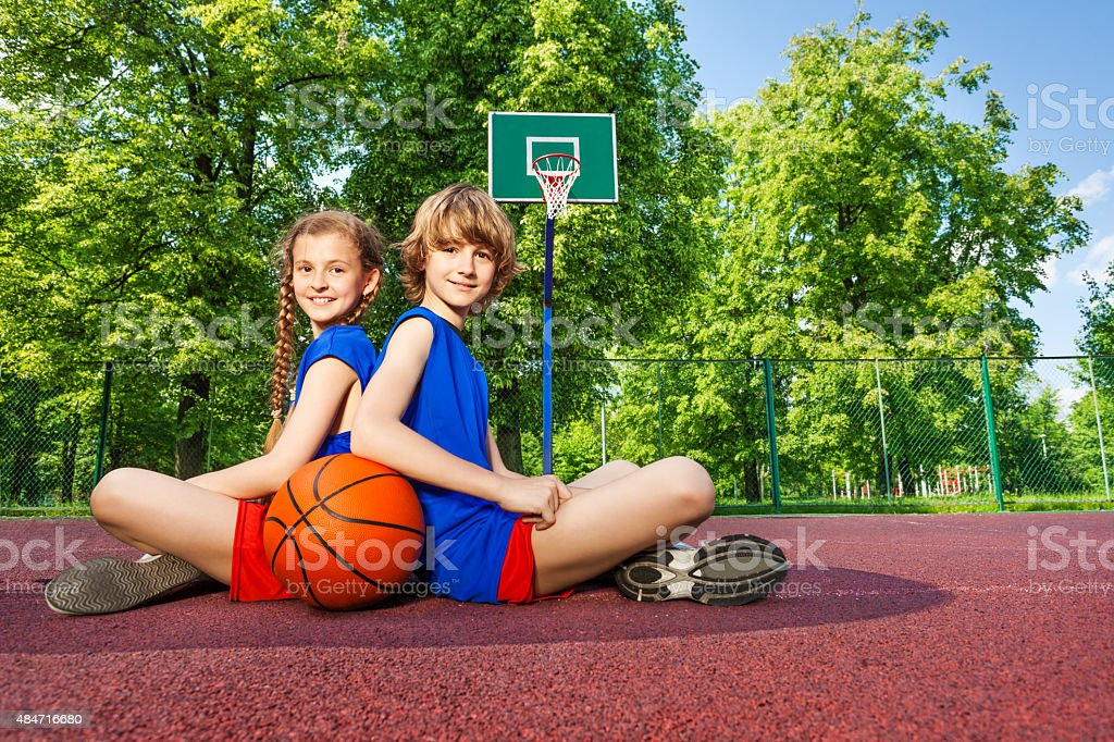 Boy and girl sit with backs close on playground stock photo