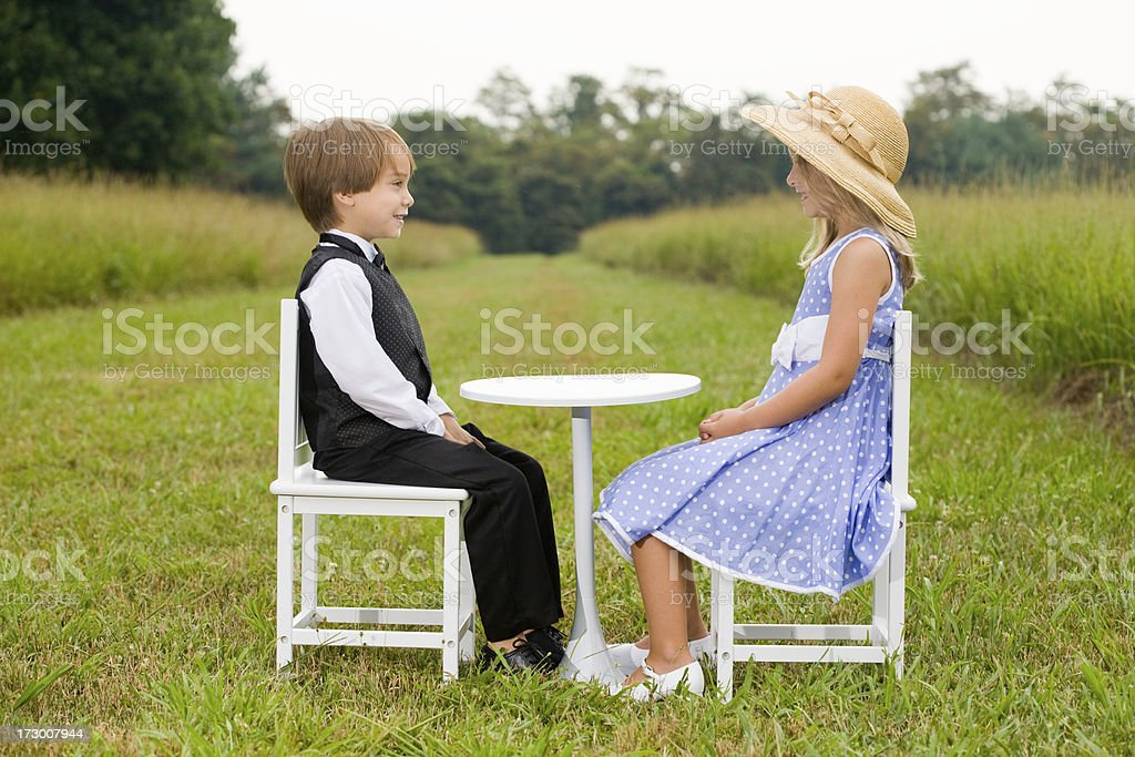 Boy and girl sitting outdoors at table hands folded royalty-free stock photo