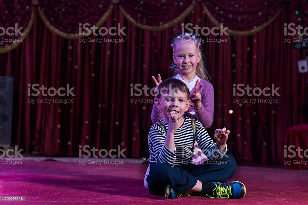 Boy and Girl Sitting Together on Stage stock photo
