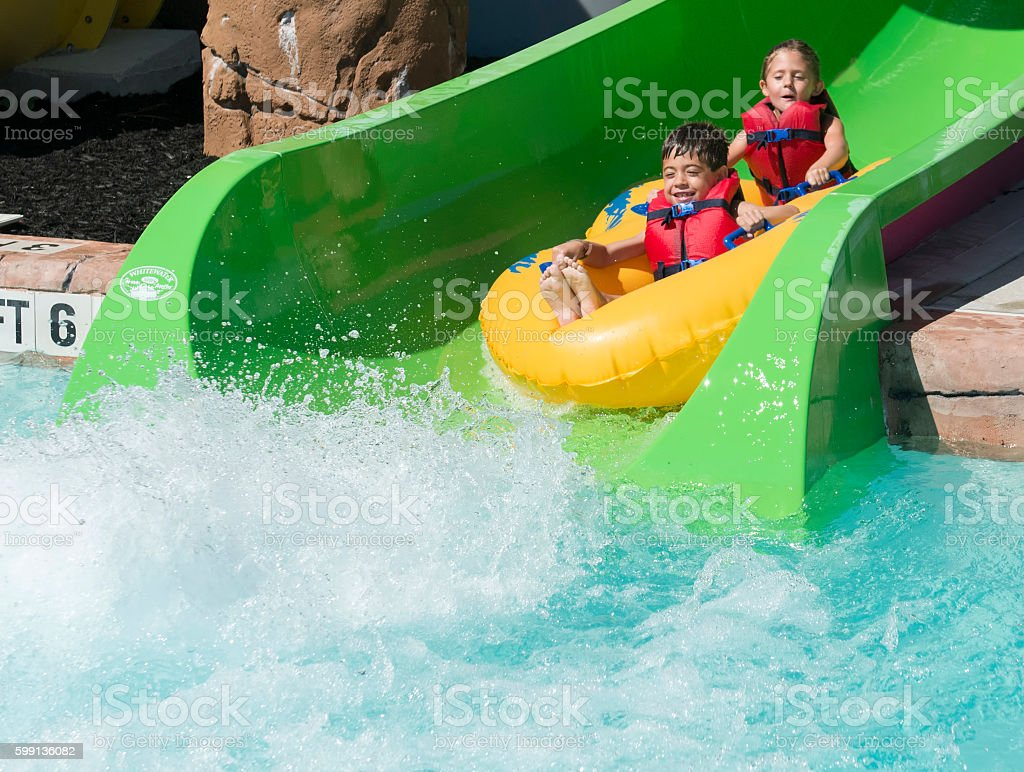 Boy and girl sliding into a pool on a raft stock photo