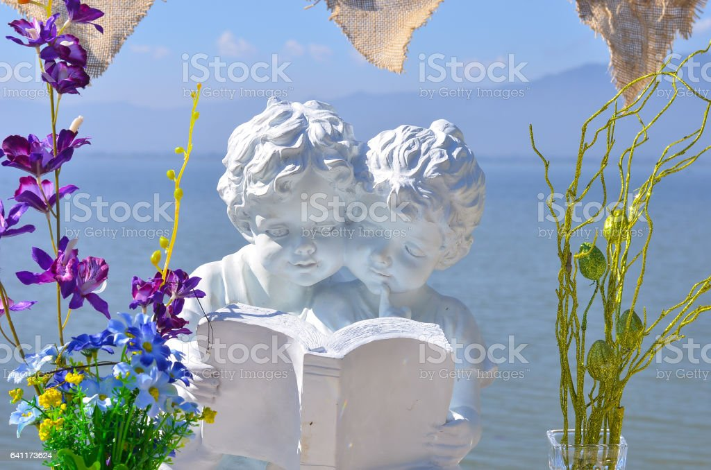 boy and girl statue read  book stock photo