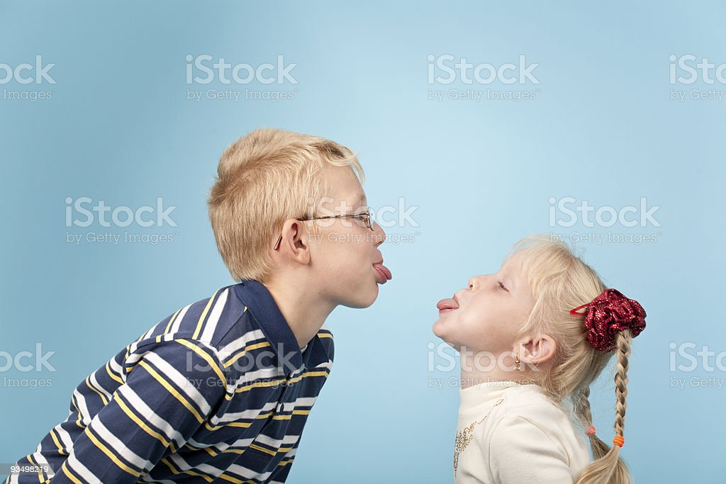 A boy and girl sticking their tongues out at each other royalty-free stock photo