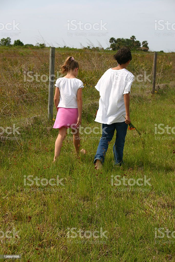 Boy and Girl Walking in a Field royalty-free stock photo