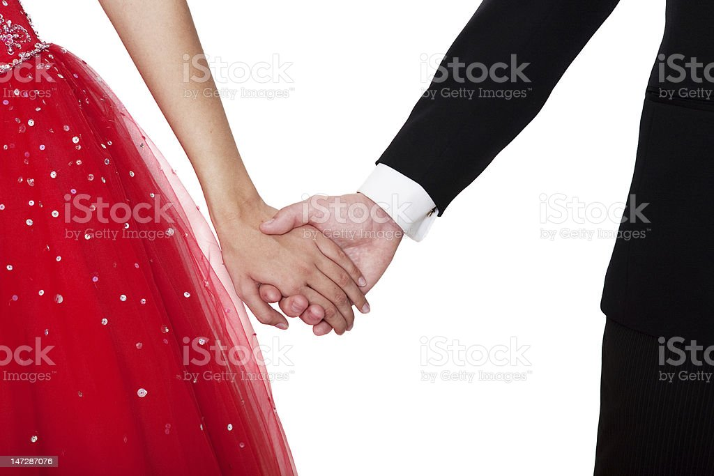 Boy and girl wearing prom outfits holding hands stock photo