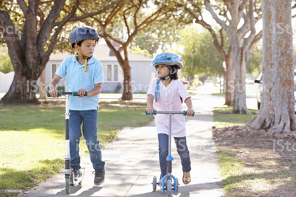 Boy And Girl Wearing Safety Helmets Riding Scooters stock photo