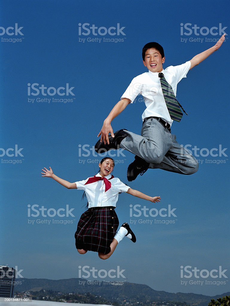 Boy and Girl (12-14) wearing school uniform, jumping in air, portrait stock photo