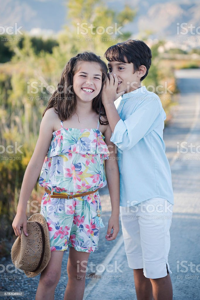Boy and girl whispering stock photo
