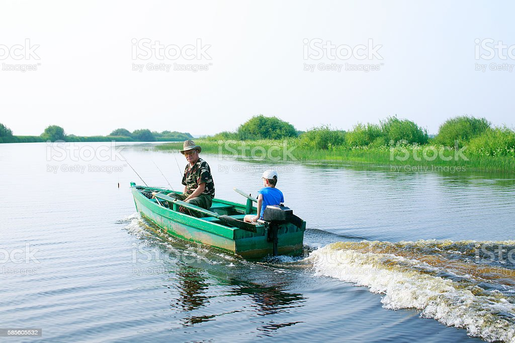 boy and his grandfather drives a motor boat stock photo