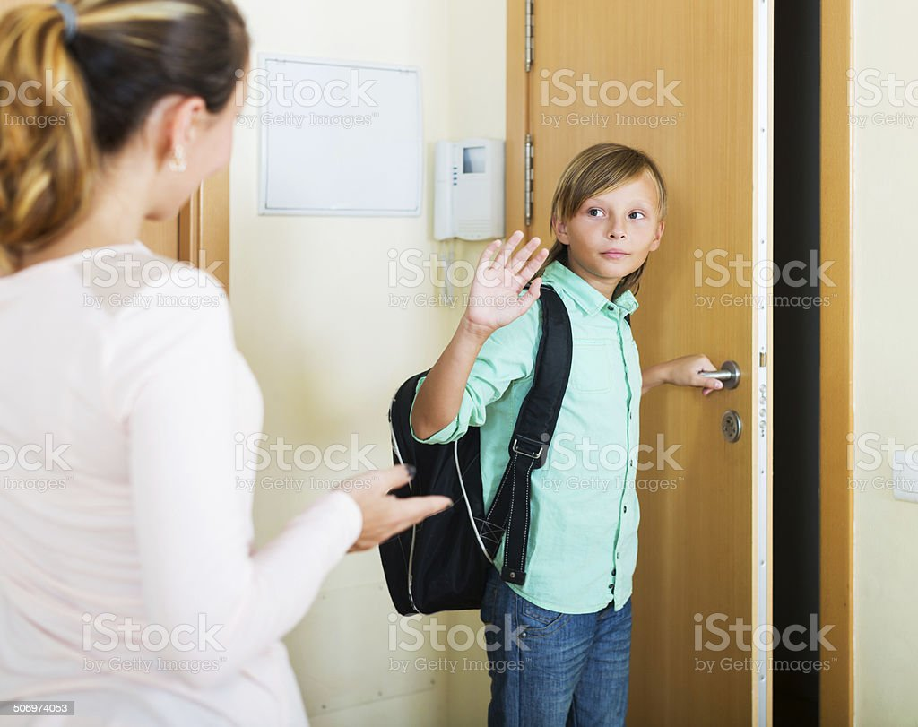 Boy and his mother staying near flat entrance stock photo