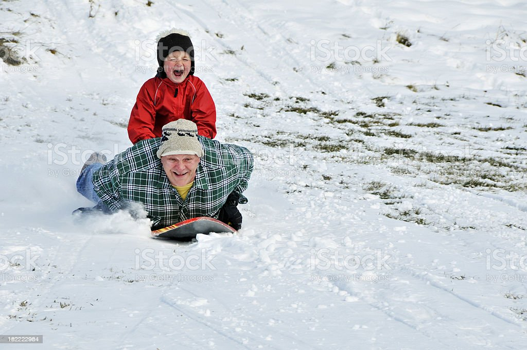Boy and man sled down a hill royalty-free stock photo