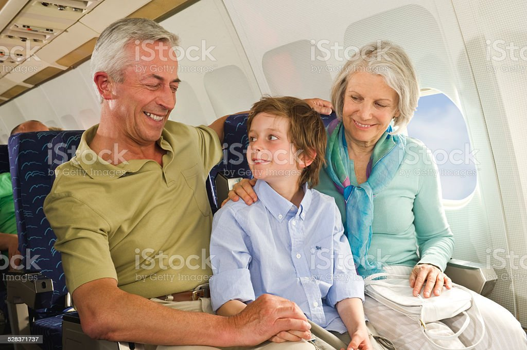 Boy and senior people smiling  on airplane stock photo
