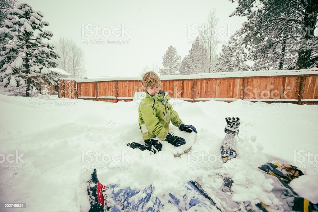 Boy and sister playing in snow in backyard stock photo