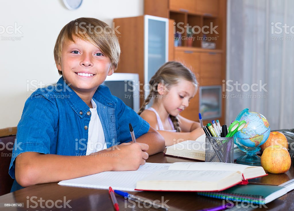 boy and sister studying with books stock photo