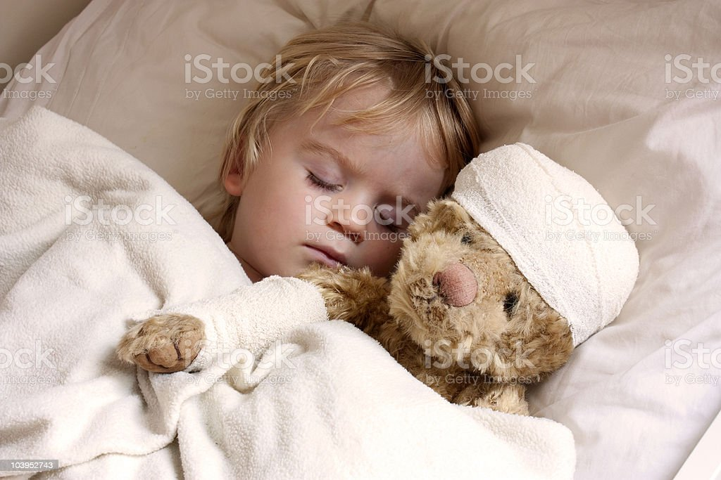 boy and teddybear in bed stock photo