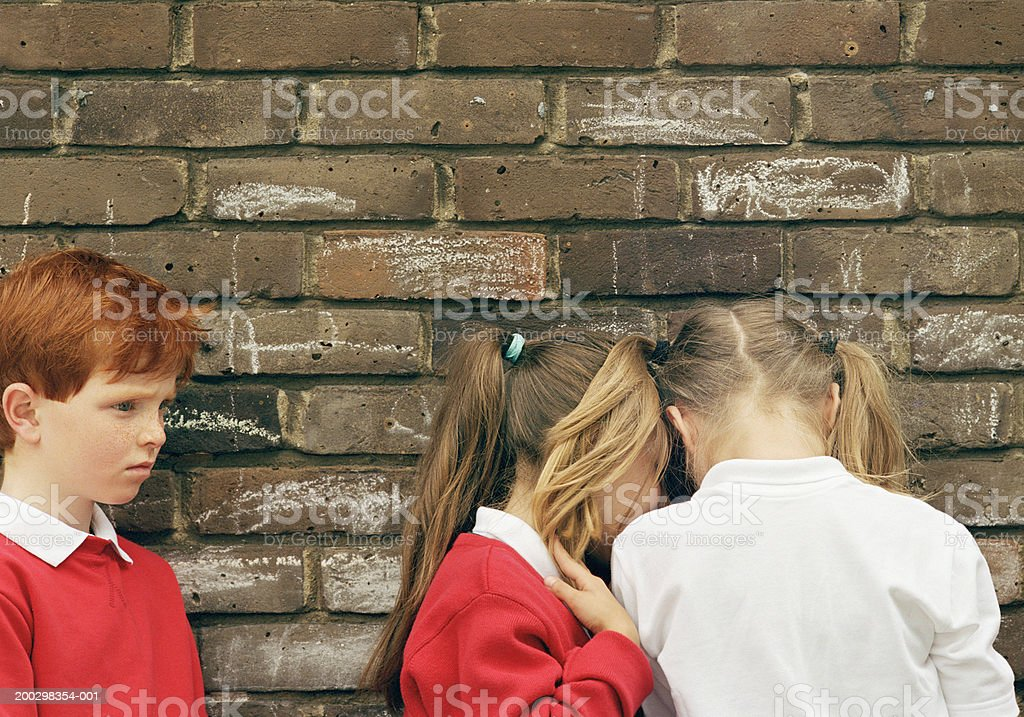 Boy (5-7) and two girls (6-8) standing by wall royalty-free stock photo