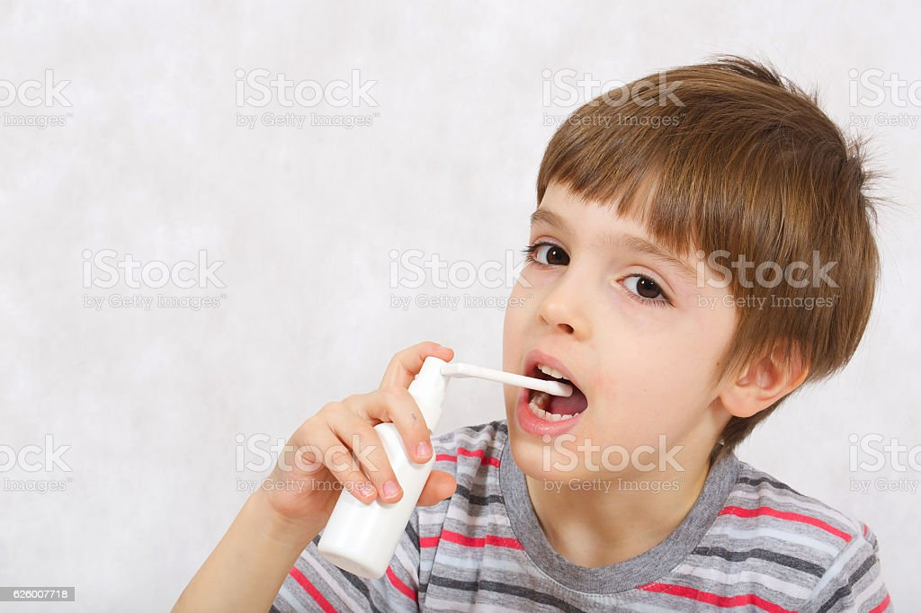 Boy applies a throat spray to relief a pain stock photo