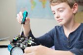 Boy Assembling Robotic Kit In Bedroom