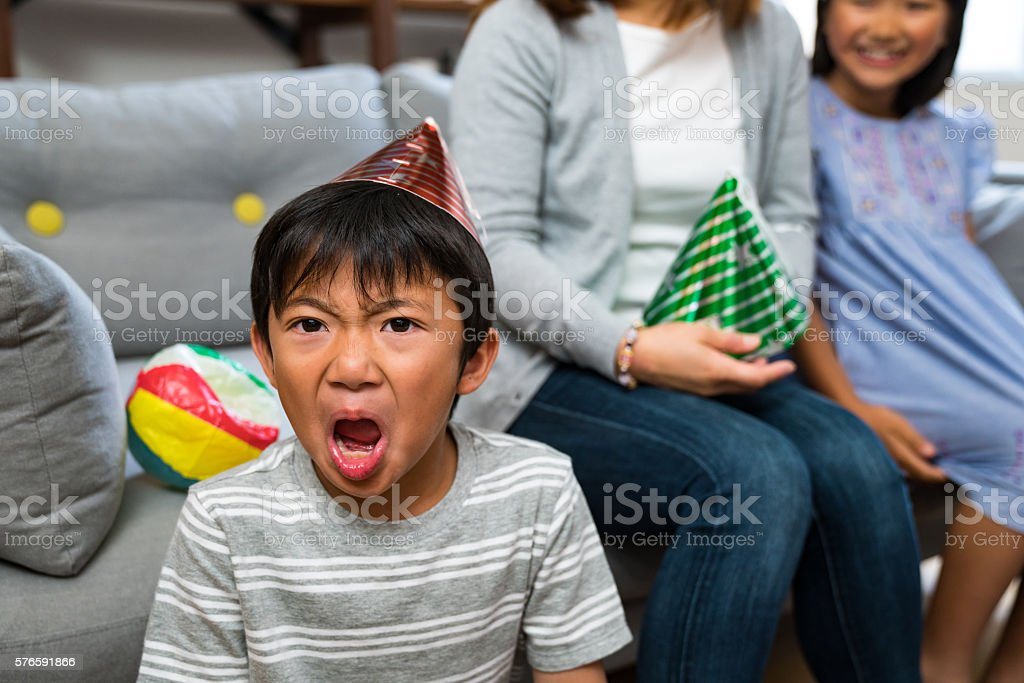 Boy at a party looking very angry and upset stock photo