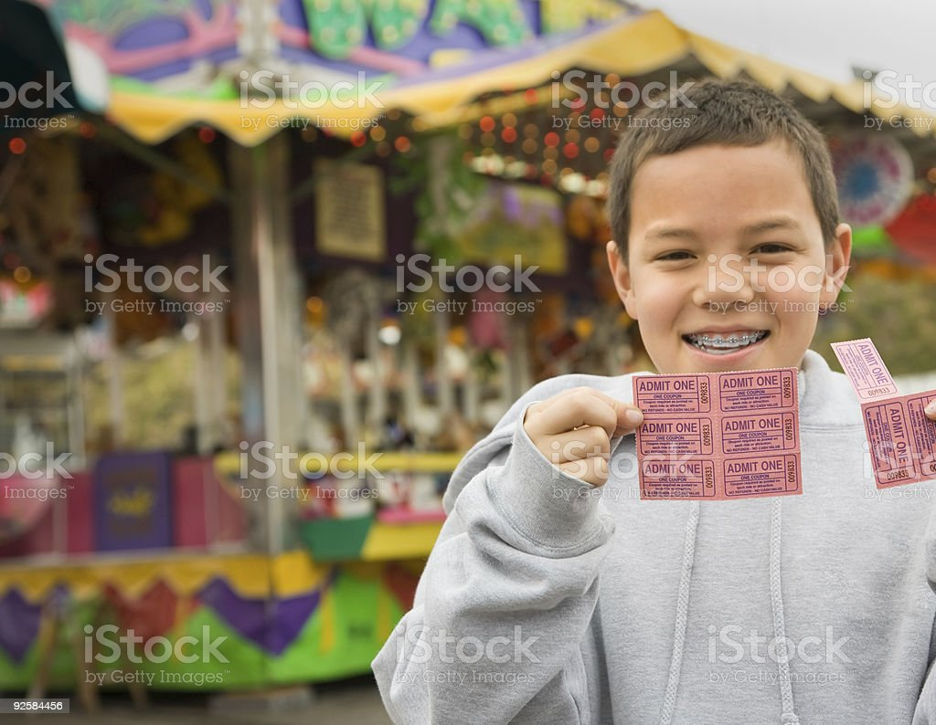Boy at carnival with tickets stock photo