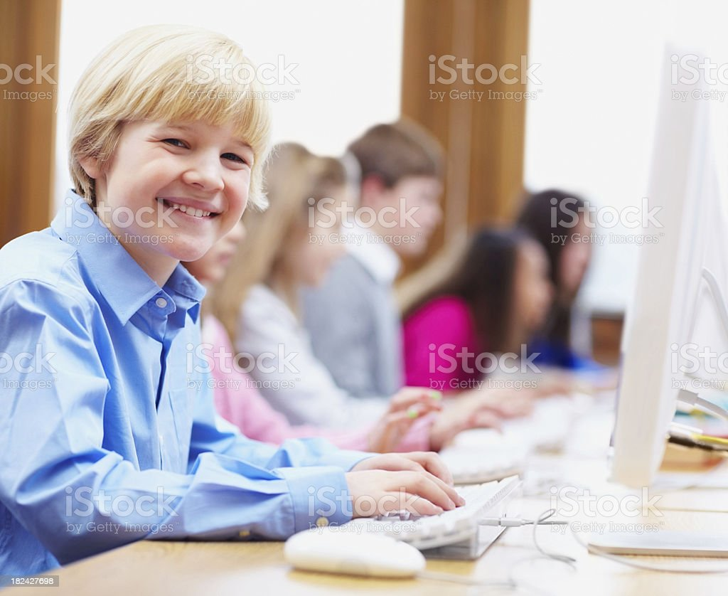 Boy at computer class with friends behind him royalty-free stock photo