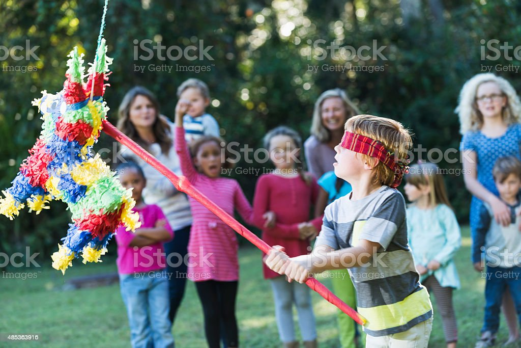 Boy at party hitting pinata with stick stock photo