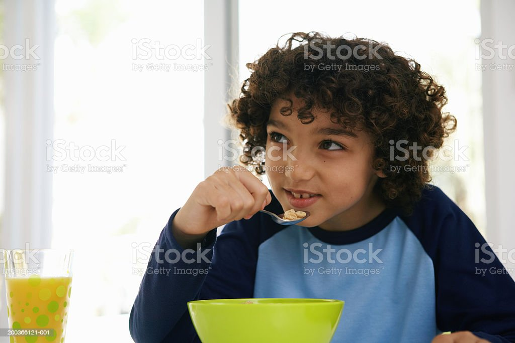 Boy (8-10) at table, eating cereal royalty-free stock photo