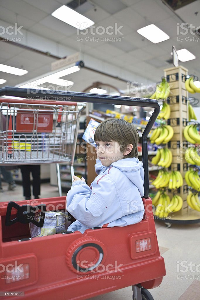 Boy at the supermarket with a shopping cart royalty-free stock photo