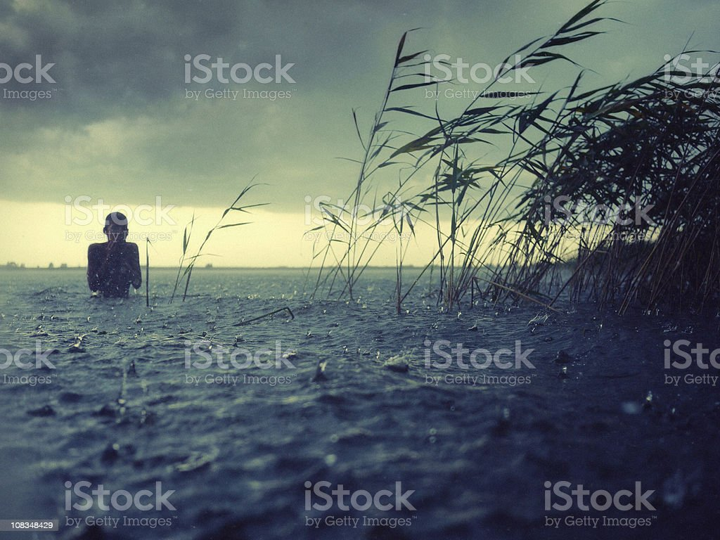 boy at water in the rain royalty-free stock photo