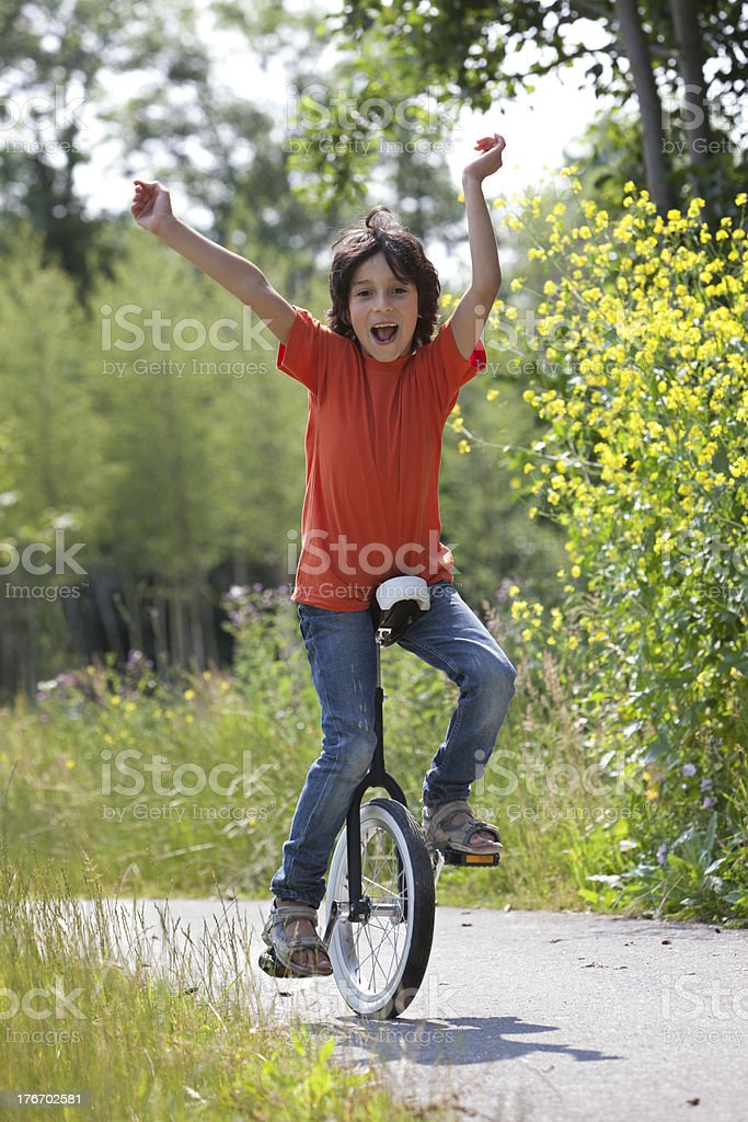 Boy balancing on a unicycle stock photo