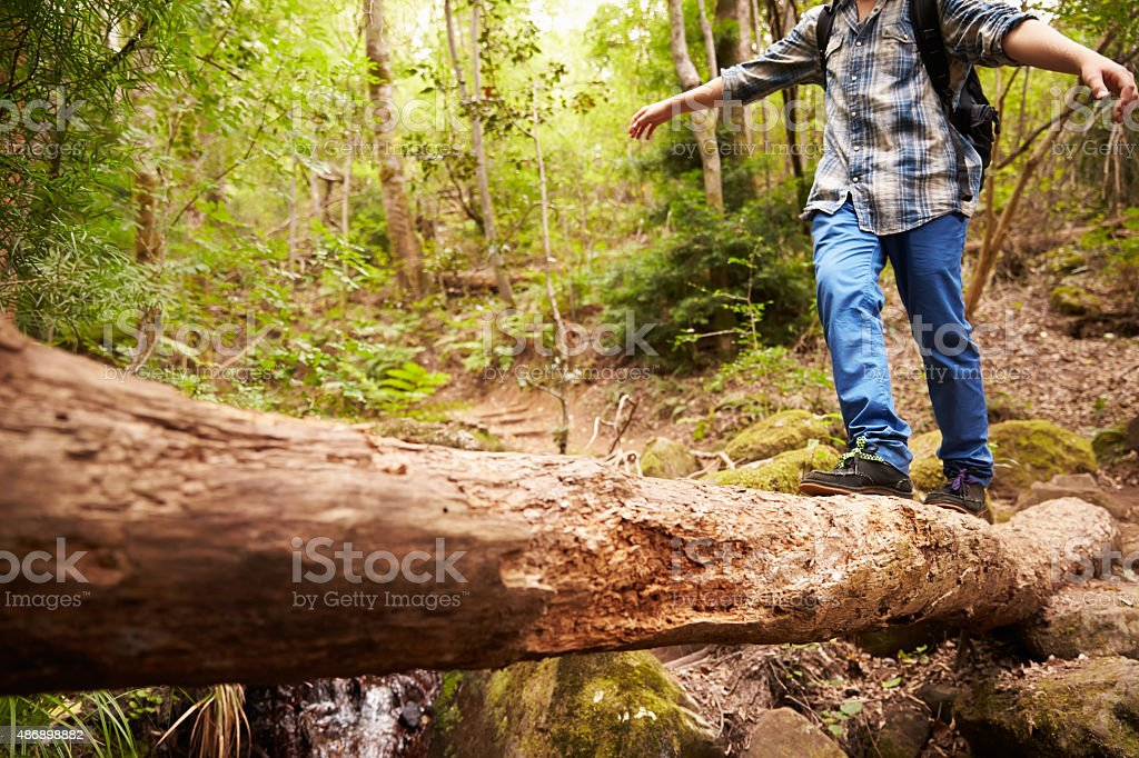 Boy balancing on fallen tree to cross stream in forest stock photo
