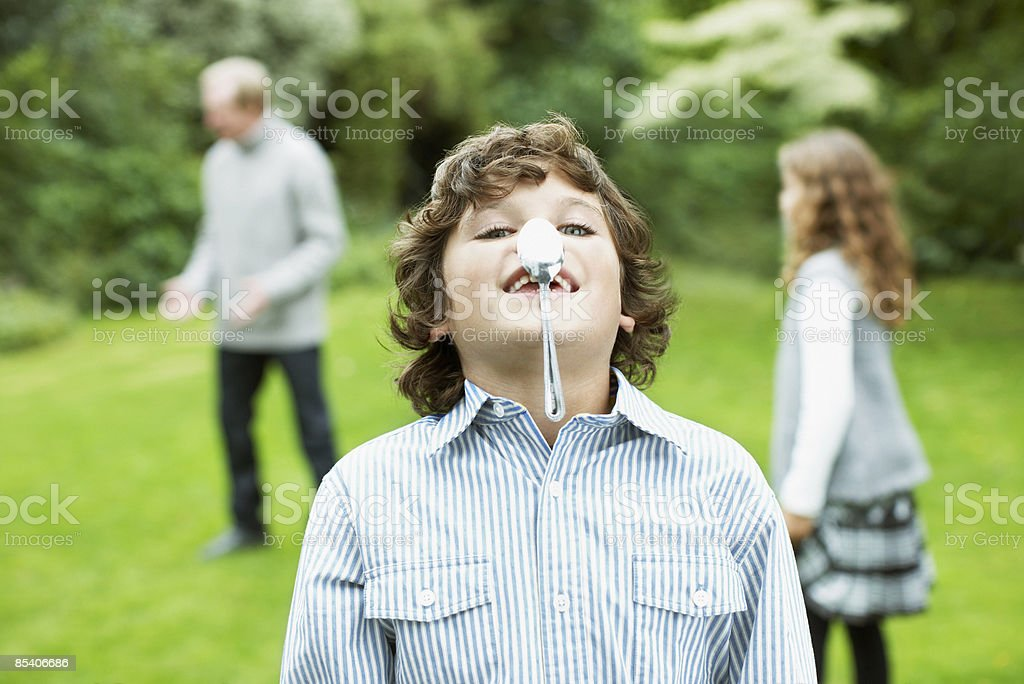 Boy balancing spoon on nose royalty-free stock photo