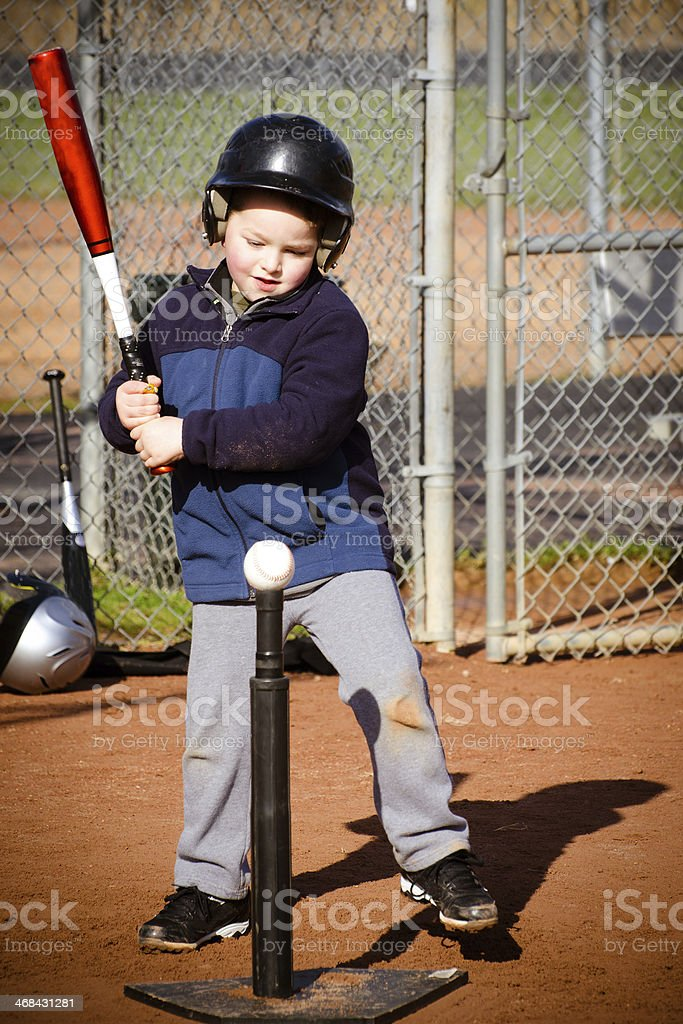 Boy batting at T-ball practice stock photo