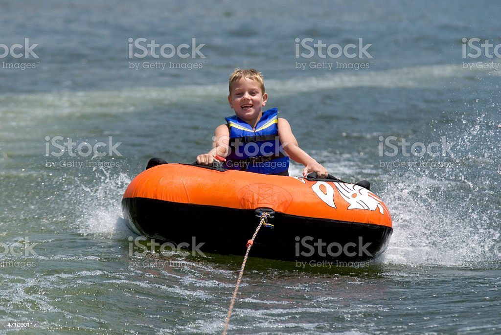Boy behind boat in inner tube royalty-free stock photo