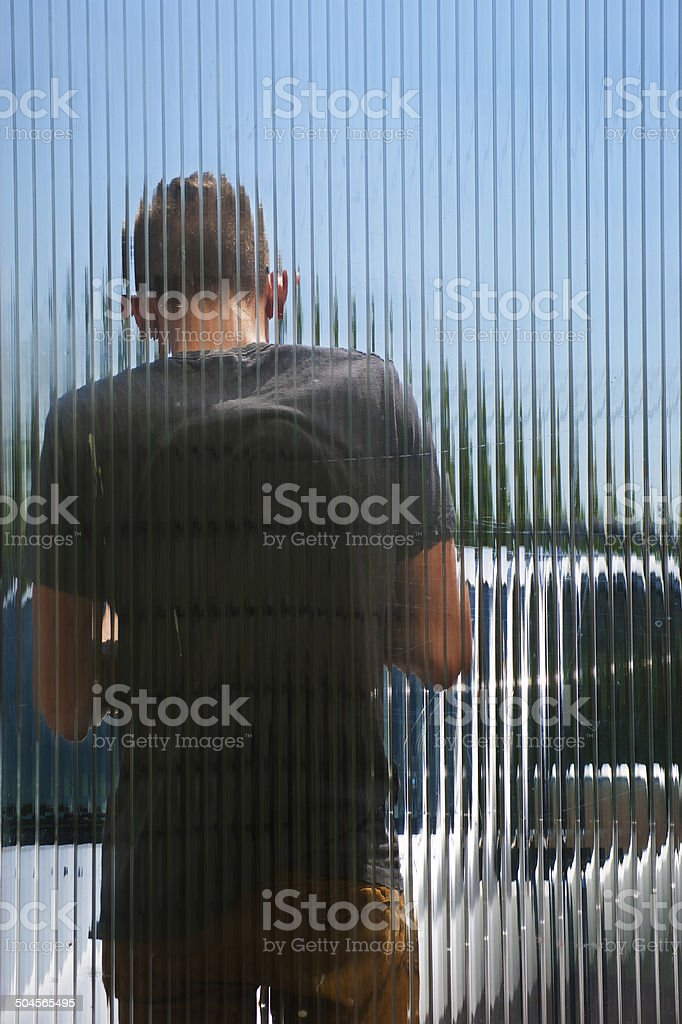 Boy behind the glass chamber polycarbonate stock photo