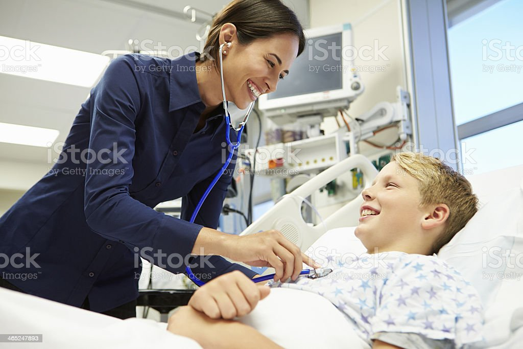 Boy Being Examined By Female Consultant In Emergency Room stock photo