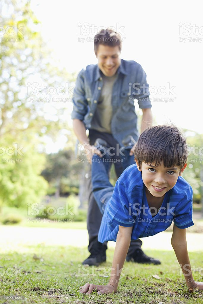 Boy being held up by the feet stock photo