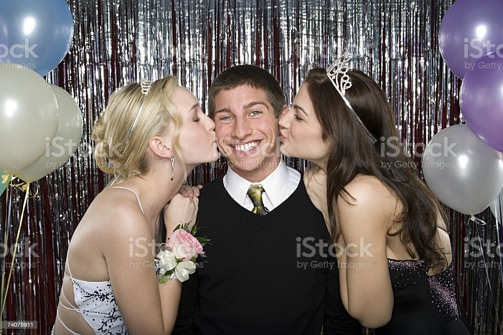 Boy being kissed by two girls stock photo